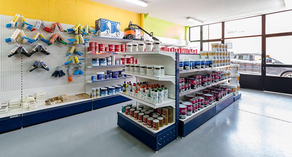 Una estanteria de una tienda de pinturas llena de botes y herramientas para pintar