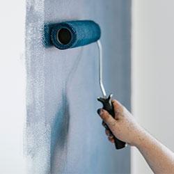 Una persona pintando la pared con pintura de decoración azul