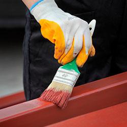 Una persona pintando una barra de hierro con pintura industrial de color roja